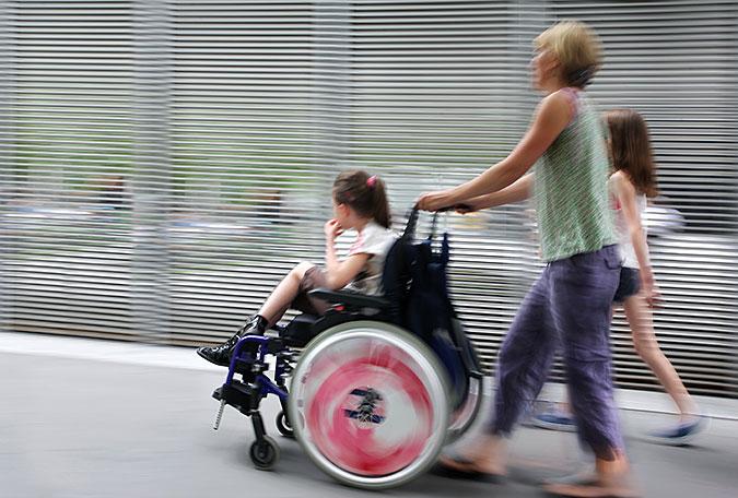 Flicka i rullstol blir körd av kvinna.
