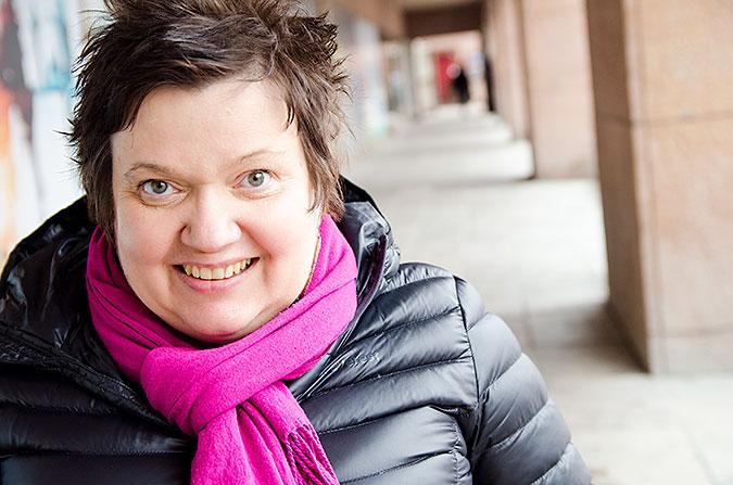Sari Nykvist iklädd svart jacka och rosa halsduk. HOn sitter utomhus med en arkadgång i bakgrunden.