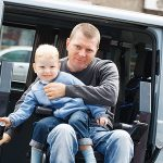 En man kör sin rullstol ut ur bilen på en lift montread vid en skjutdörr. I knät harhan ett barn.