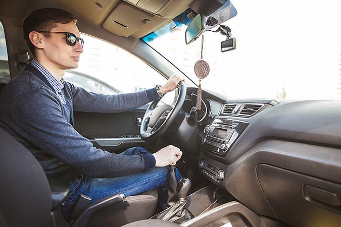 En man med solglasögon kör bil med ett handreglage till gas och broms.