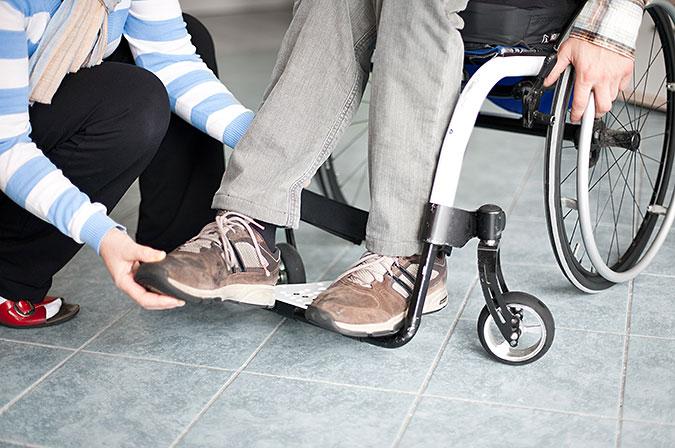 En person som sitter i rullstol får hjälp att få foten på plats på fotplattan.