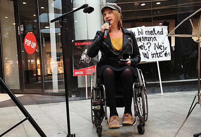 En kvinna sitter i rullstol och pratar i en mikrofon. I bakgrunden står några plakat lutade mot en glasvägg.