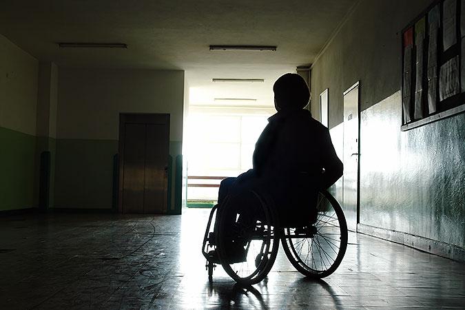 Person sitter i rullstol i en mörk och kal korridor där det enda ljuset kommer från ett fönster i bakgrunden.