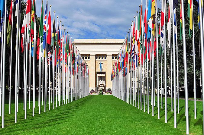 En lång alle av flaggstänger med olika nationerna fanor leder fram till en pampig byggnad i sten.