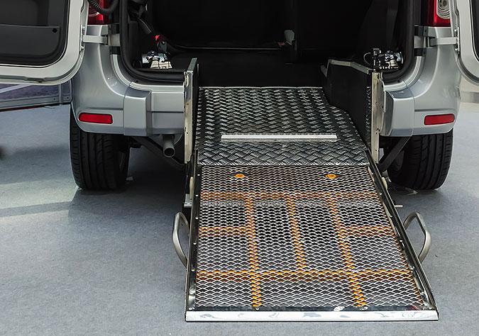 En bil som har en rullstolsramp monterad i aktern.