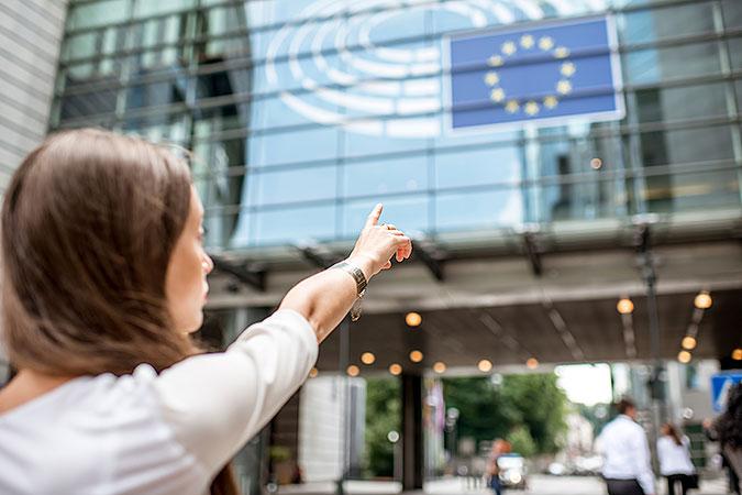 En kvinna pekar mot en fasad där det hänger en EU-flagga.