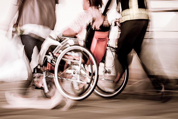 En oskarp bild på en person i rullstol som blir körd av en annan person.