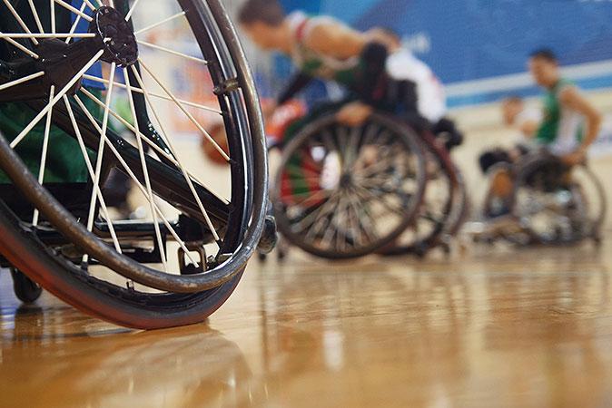 Bild i grodperspektiv på personer i rullstolar som utövar sport i en idrottshall.