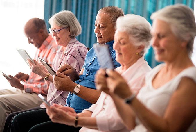 Ett gäng äldre människor sitter och interagerar med var sin mobiltelefon eller surfplatta.