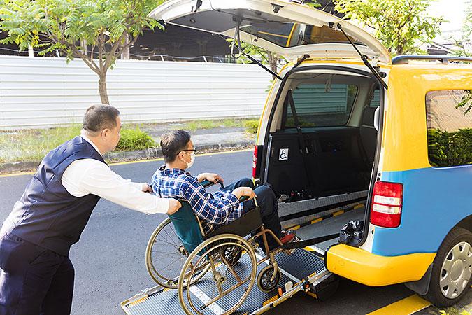 En färdtjänstchaufför hjälper en man i rullstol ombord i en liten gul och blå bil.