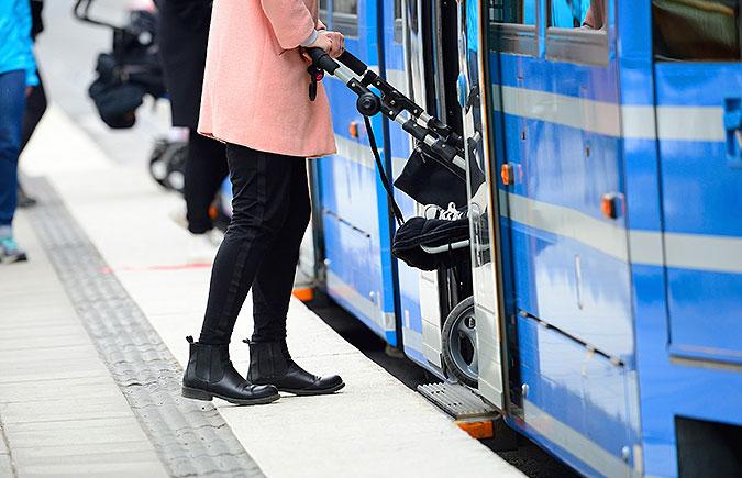 En person som skjuter en barnvagn framför sig går om bord på en spårvagn där det finns ett uutfällbart fotsteg som överbryggar avståndet mellan vagnen och perrongen.