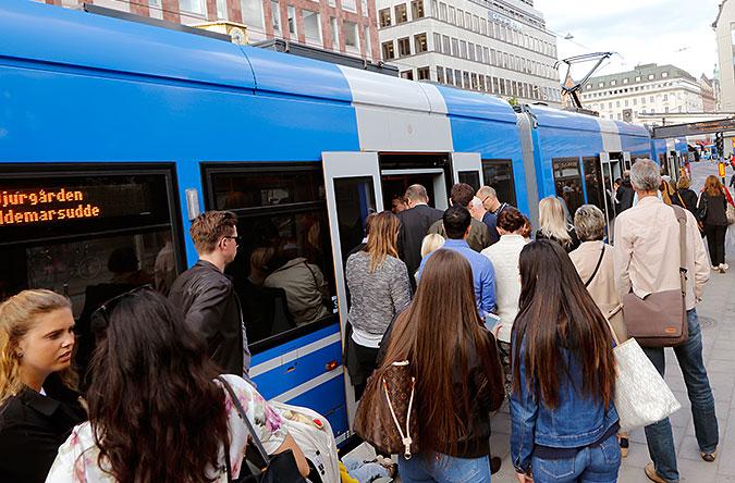En stor mängd människor köar för att komma ombord på en spårvagn.