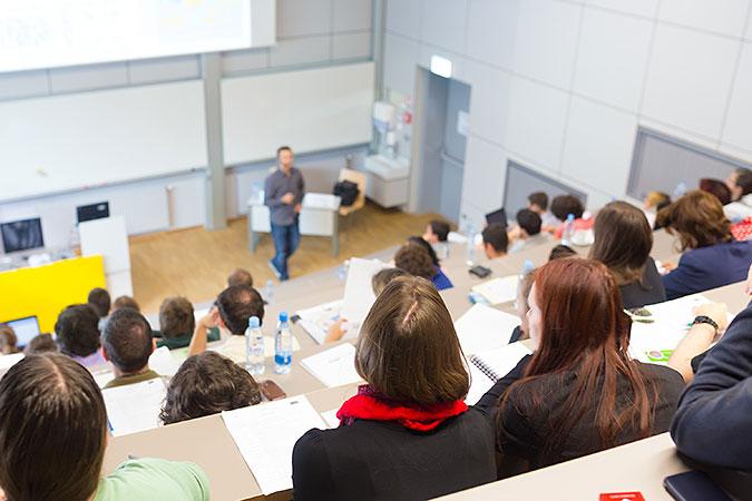 En föreläsning på ett universitet. En lärare har genomgång för studenter som sitter på en gradäng och antecknar.