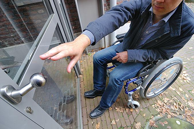Man sittande i rullstol försöker att öppna en ytterdörr.