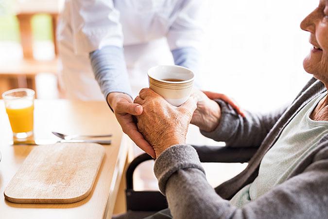 En person hjälper en äldre person att hålla en mugg med kaffe