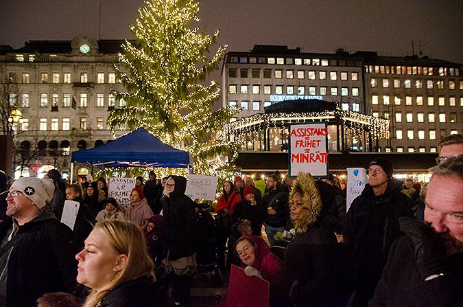 Människor med plakat där det står bland annat assistans är frihet står i mörkret på ett torg. I bakgrunden hus och en stor ljusbehängd julgran.
