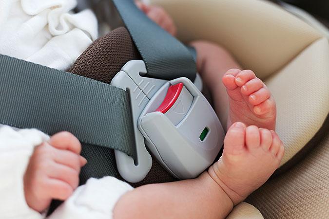 En närbild på ett mycket litet barn som är fastspänt i en bilbarnstol