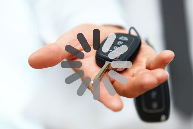 En hand håller fram ett par bilnycklar. Ovanpå bilden ligger ett markering som på en dator eller mobiltelefon brukar indikera väntan medan bilden laddas.