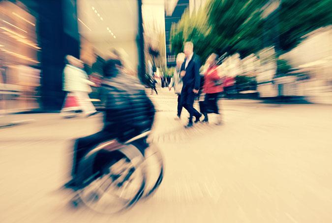 En person i rullstol tar sig fram på gatan bland andra människor. Bilden är tagen med en effekt som gör att det ser ganska stressigt ut.