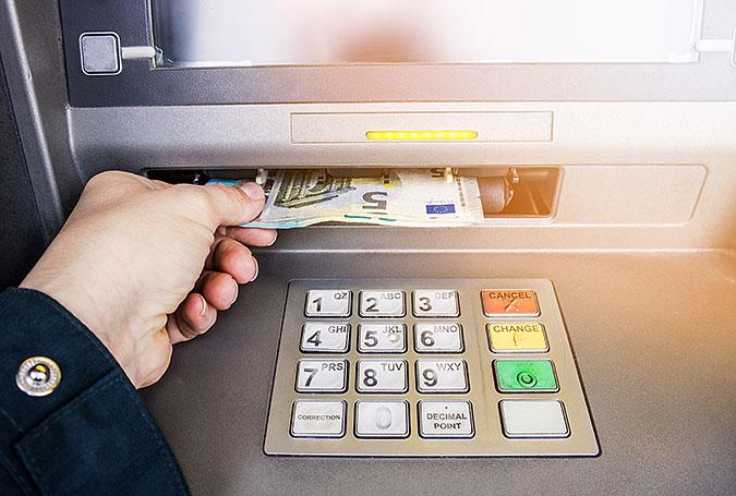 En hand tar ut euro-sedalr ur en bankomat. På bilden syns även knappsatsen.