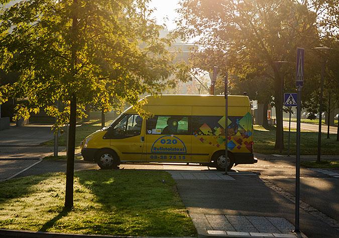 En färdtjänstbuss rullar på en väg omgiven av träd och gräsmattor.