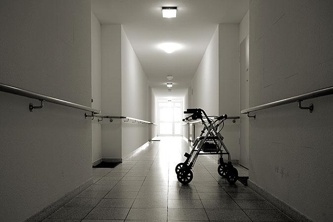 En rollator står parkerad i en i övrigt tom och kal korridor. Längs väggarna finns ledstänger.