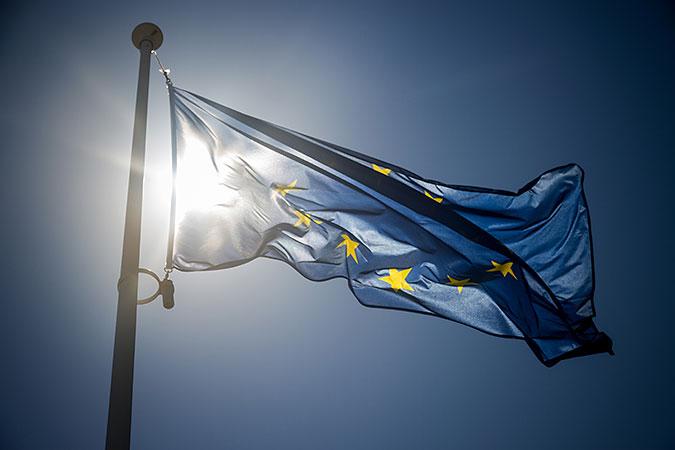 En EU-flagga fladdrar i vinden med solen i bakgrunden.