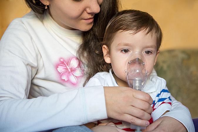 En vuxen hjälper ett barn med en andningsmask.