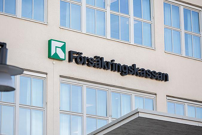 En skylt i form av Försäkringskassans logotyp på en äggskalsvit fasad med många fönster.