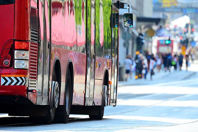 En röd buss kör på gata i stan.