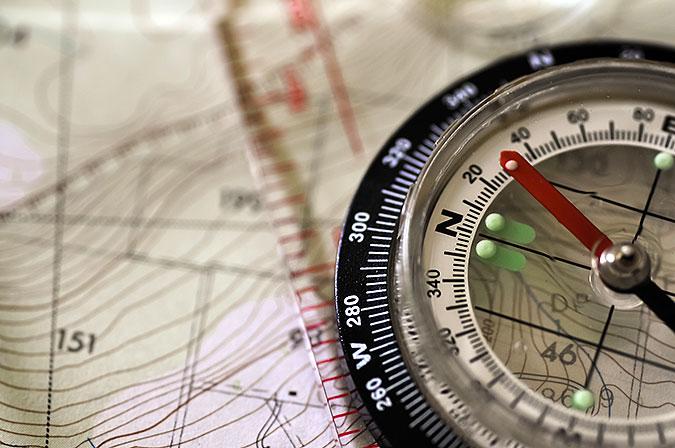 En handkompass ligger på en karta.