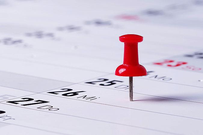 En röd nål sitter i en papperskalender.