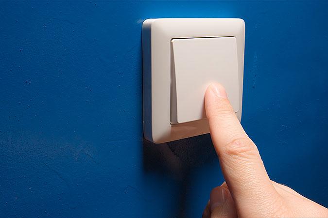 Ett finger trycker pop en strömbrytare på en blå vägg.