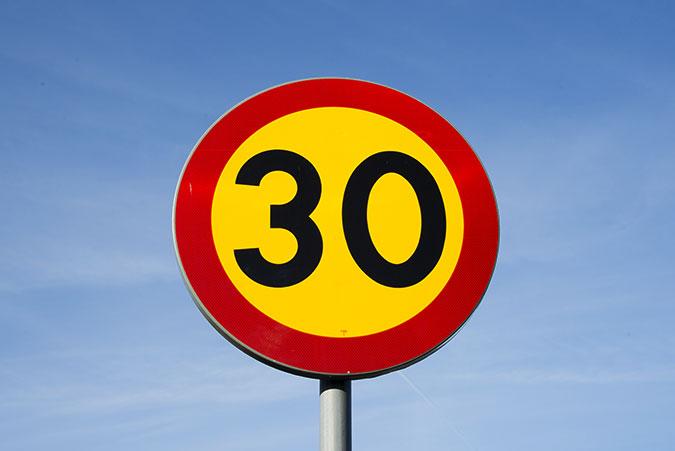 En vägskylt för hastighetsbegränsning 30-väg.
