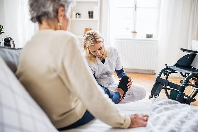 En yngre kvinna från hemtjänsten hjälper en äldre kvinna som sitter i en säng att sätta på sig tofflorna. Bredvid sängen står en rullstol.