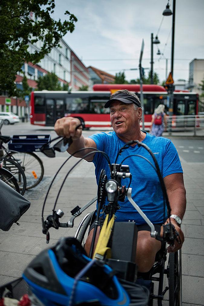 Björn Billung i gatumiljö. I bakgrunden ser man en röd linjebuss och till vänster ett cykelställ med några parkerade cyklar.