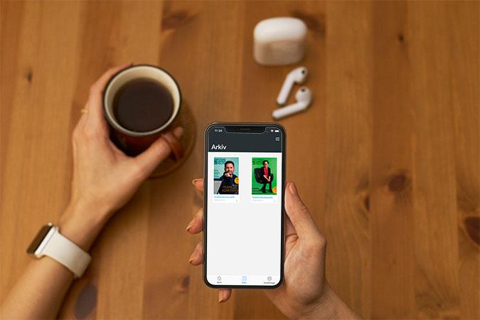 En person håller en mobiltelefon i ena handen där man ser Funktionshinderpolitiks nya upplösning. I andra handen håller personen en kaffekopp.
