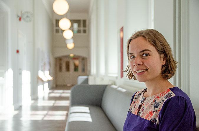 Marie Séplchre sitter i en soffa i en korridor där stora fönster släpper in ljuset från solen.