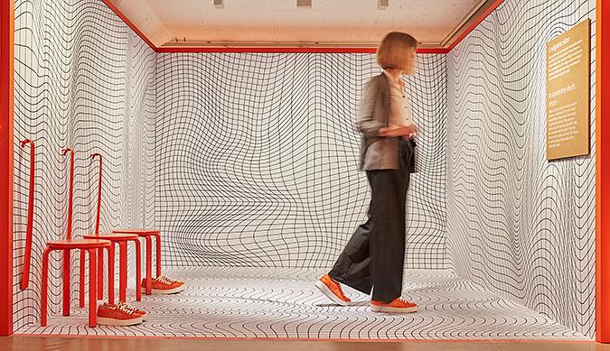 En person går i ett litet rum med ett oregelbundet rutnätsmönster på väggar och golv. Till vänster i bild står tre orangefärgade pallar med var sitt par orangefärgade skor.