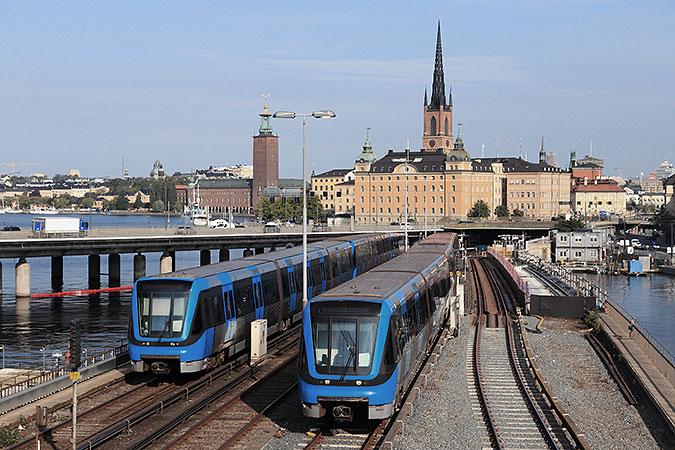 Två tunnelbanetåg kör på bron mellan slussen och gamla stan. I bakgrunden syns Stadshuset och riddarholmen.