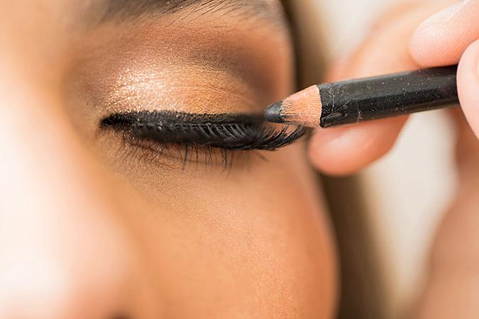En närbild på ett ansikte där någon målar med en penna på ögonlocket.