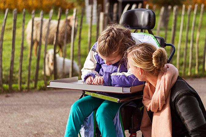 En flicka sitter i en rullstol. Bredvid henne sitter en kvinna och ser ut att prata med flickan. Ibkagrunden ser man två får bakom ett staket.