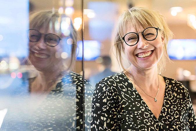 Porträtt av Åsa Nillson Billme som står lutad mot en glasruta där hennes bild reflekteras.