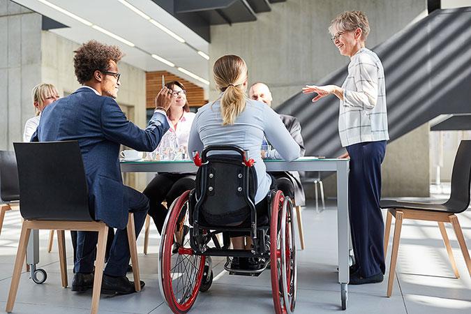 Sex personer runt ett bord på vad som ser ut att vara ett väldigt sparsmakat kontor. En av personerna sitter i rullstol.