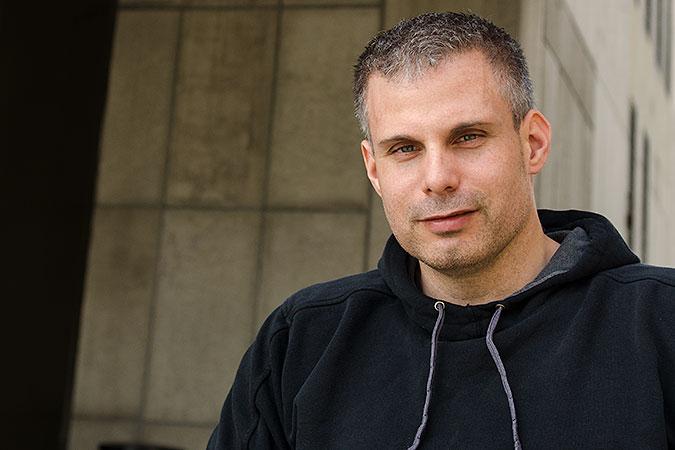 Porträtt av Rasmus Isaksson framför en grå byggnad i betong.