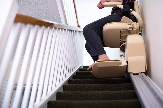 En person är på väg uppför en trappa med hjälp av en trapplift.Trappan är ganska typsik för de som finns i mindre villor eller radhus. Bilden är tagen nerifrån och personen syns inte i sin helhet.
