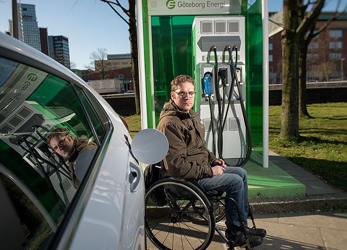 En man sitter i rullstol bredvid en vit bil. Bakom honom står en snabbladdare för elbilar på ett betongfundament. Fundamentet gör att mannen inte når laddaren.