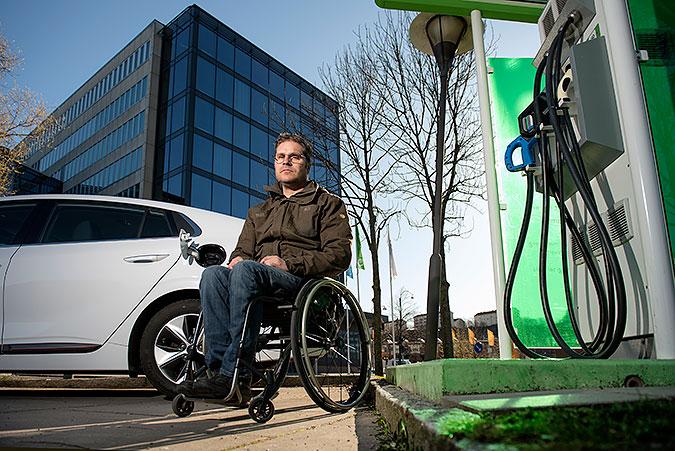 En man sitter i rullstol bredvid en snabbladdare. Bakom mannen står hans vita bil. iI bakgrunden ett kontorshus. sSnabbladdaren står på ett betongfundament och 'r utom räckhåll för mannen.