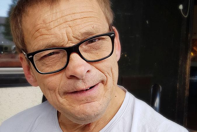 Ett porträtt av en man i glasögon med mörk båge.