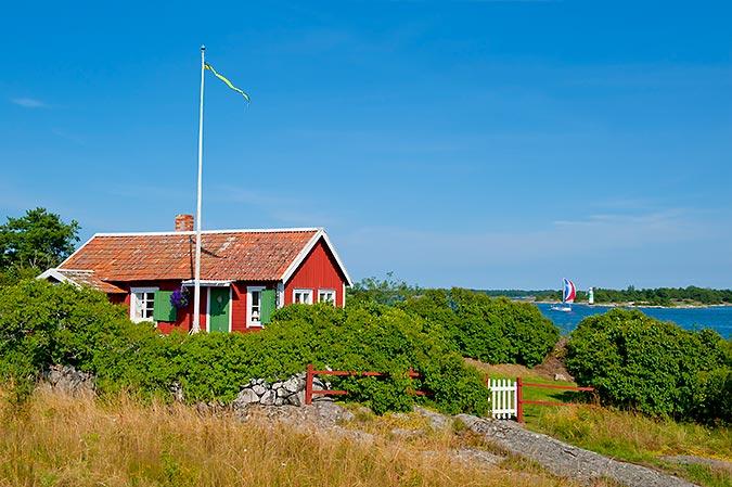 En röd stuga med vita knutar ligger inbäddad i grönska  alldeles bredvid kusten. I bakgrunden syns en segelbåt med spinnaker passera en lite fyr. Himmelen är blå.
